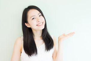 左手のひらを上に向ける笑顔の女性