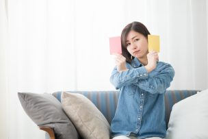 ソファに座りカードを見せるデニムシャツの女性