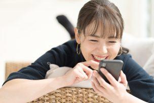 寝ころびながらスマートフォンを操作する女性