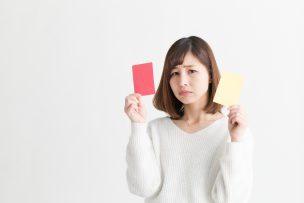 赤と黄色のカードを持った女性